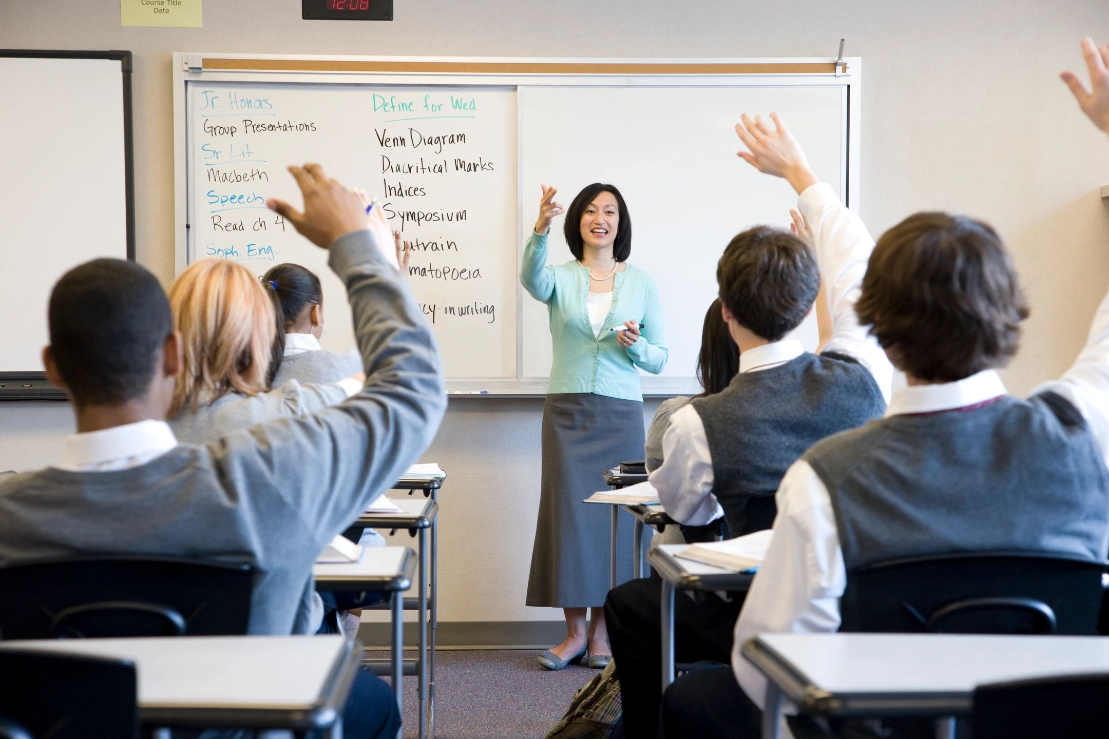 UK Boarding School students raising their hands in class